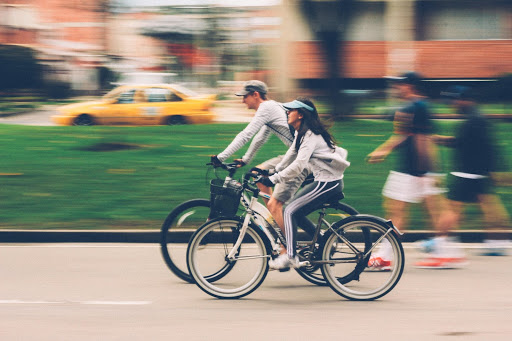 Woman and Man Riding on Bike by Nubia Navarro